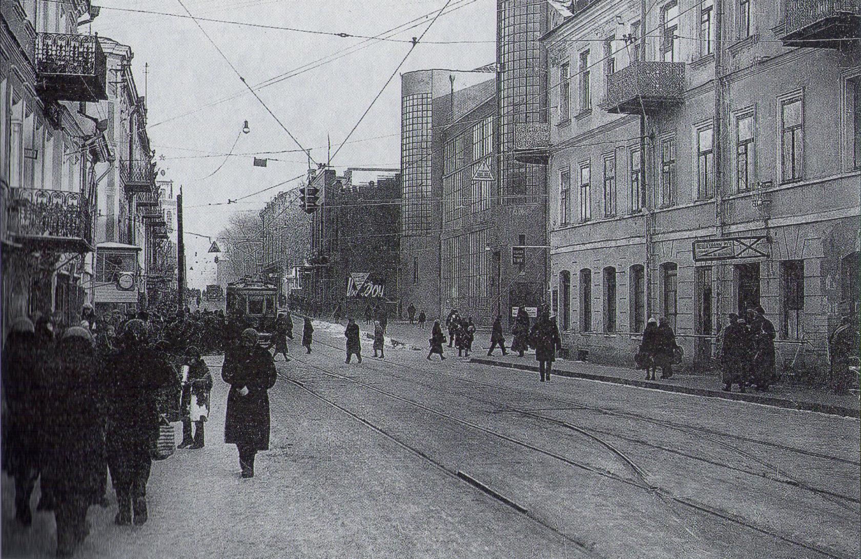 На перекрёстке улиц Советской и Ленинской был установлен один из первых минских светофоров. Справа видно оригинальное здание в конструктивистском стиле. Здесь размещалась белорусская контора Госбанка СССР. К сожалению, разрушенное в войну здание не стали восстанавливать и вместе с другой застройкой улицы Советской снесли. Фото 1933 года.