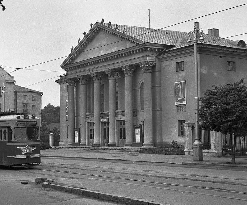1960-й, трамвай идёт по улице Козлова около Дворца культуры строителей. В то время здесь работали кружки, курсы, проходили концерты. В 1986 году здание закрыли на реконструкцию, а в 1991-м и вовсе законсервировали. Почти 20 лет здание стояло без дела и разрушалось. В 2010 году его решили восстановить и отдать Молодёжному театру.
